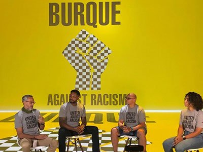 People in chairs with Burque Against Racism on screen in background