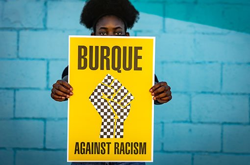 woman holding burque against racism poster