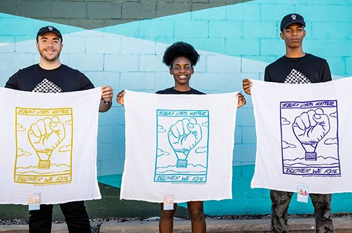 people holding tea towels with balloon fist graphic